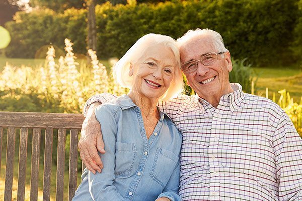 Elder Law & medicaid planning concept - happy, loving elder couple sitting outside on park bench