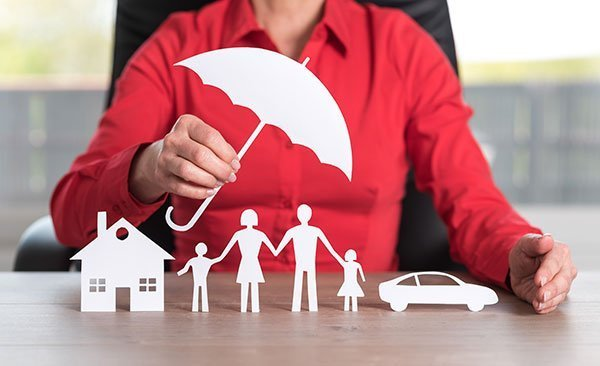 Asset protection concept - woman holding paper cut out of umbrella over public cutouts of a family, home and car