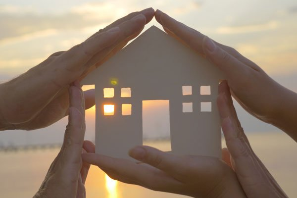 Estate Planning concept - two sets of hands holding up a cutout of a house
